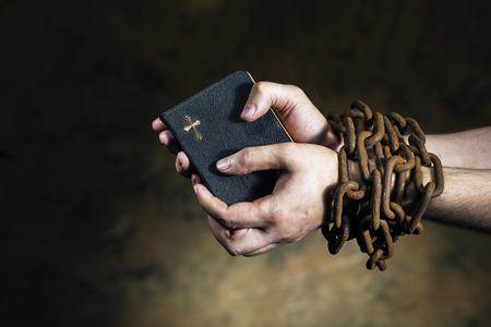 cadenas: Manos que sostienen una biblia atadas con una cadena oxidada de edad. Foto de archivo
