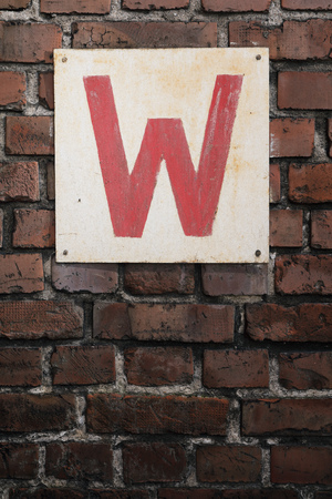 brick sign: Old sign with letter W on a brick wall.