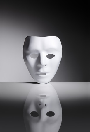 reflective: White blank plastic mask on reflective surface. Stock Photo