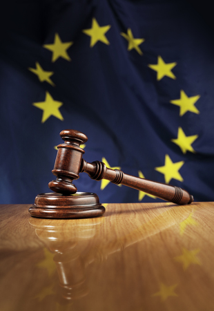 court: Mahogany wooden gavel on glossy wooden table. Flag of European Union, EU,  in the background.