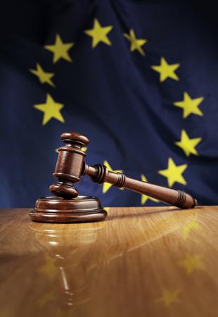justicia: Martillo de caoba de madera en la mesa de madera brillante. Bandera de la Unión Europea, UE, en el fondo. Foto de archivo