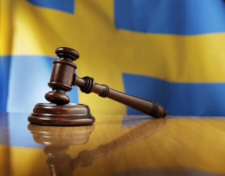 legislature: Mahogany wooden gavel on glossy wooden table, flag of Sweden in the background. Stock Photo