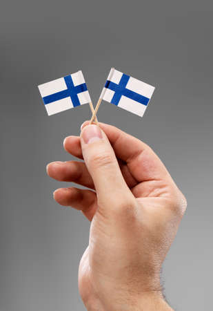 two object: Man holding two small flags of Finland in his hand.