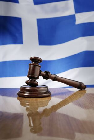 sentenced: Mahogany wooden gavel on glossy wooden table, flag of Greece in the background. Stock Photo