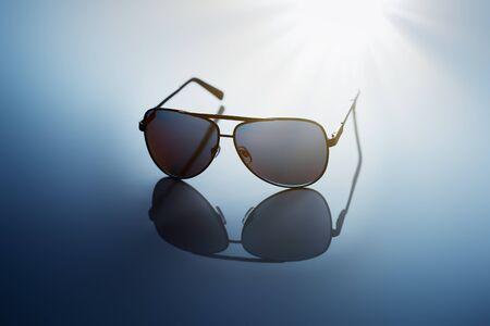 reflective: Sunglasses on blue reflective background. Stock Photo