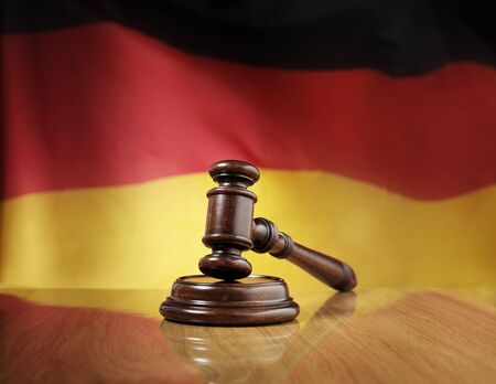 sentenced: Mahogany wooden gavel on glossy wooden table, flag of Germany in the background. Stock Photo