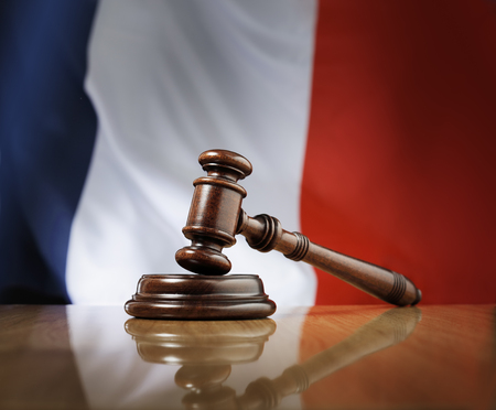 legality: Mahogany wooden gavel on glossy wooden table, flag of France in the background.