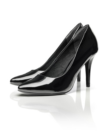 patent leather: Black shiny patent leather stiletto heel pumps isolated on white with natural reflection.