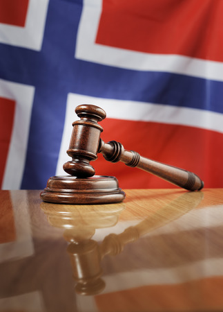 sentenced: Mahogany wooden gavel on glossy wooden table, flag of Norway in the background.