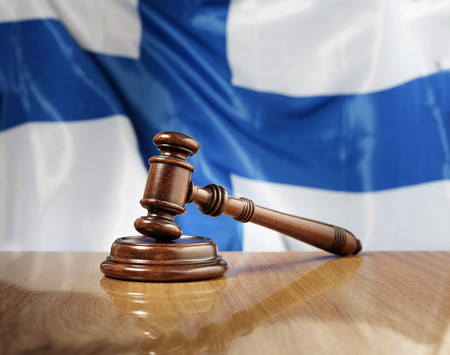 juridical: Mahogany wooden gavel on glossy wooden table, flag of Finland in the background.