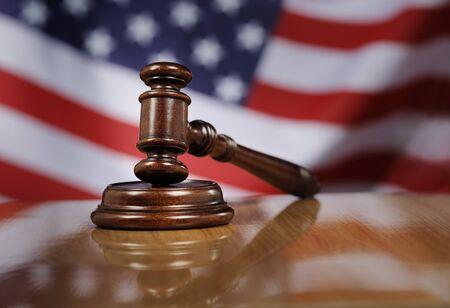 caoba: Martillo de caoba de madera en la mesa de madera brillante, bandera de EE.UU. en el fondo. Foto de archivo