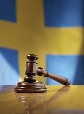 sentenced: Mahogany wooden gavel on glossy wooden table, flag of Sweden in the background. Stock Photo
