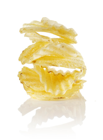 ridged: Unflavored ridged potato chips stacked on a reflective background.