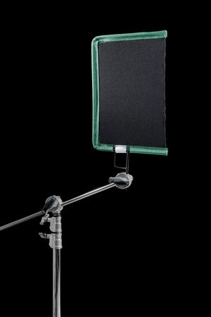 gaffer: Film lighting equipment: A single scrim mounted on a c-stand.