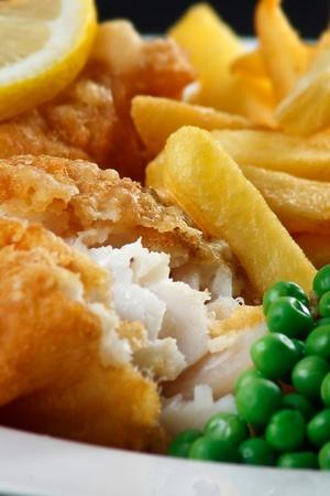 fish and chips: Cierre de pescado y patatas fritas con guisantes y una rodaja de lim�n un plato tradicional de Mar Brit�nico