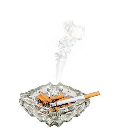 shorter: A fag burns shorter in a glass ashtray Stock Photo