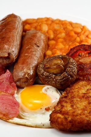 papas doradas: T�pico desayuno completo Ingl�s consiste en salchichas, bacon, huevo, champi�ones, papas, frijoles y tomate frito Foto de archivo