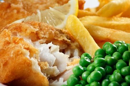 fish and chips: Cierre de pescado y patatas fritas con guisantes y una rodaja de limón un plato tradicional de Mar Británico