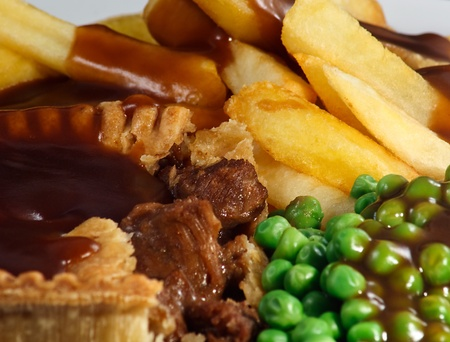 gravy: Close up of Steak Pie and chips with peas and gravy  A traditional British Dish Stock Photo