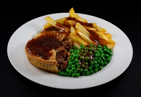 Close up of Steak Pie and chips with peas and gravy  A traditional British Dish photo