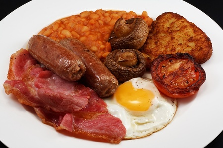 Typical full breakfast consisting of Sausage, bacon, egg, mushrooms, hash browns, beans and Fried Tomato photo