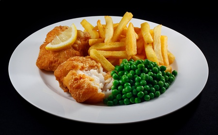 fish isolated: Close up of fish and chips with peas and a slice of lemon  A traditional British Seaside Dish
