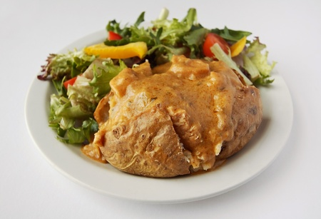 baked potato with curry filler on a plate with side salad