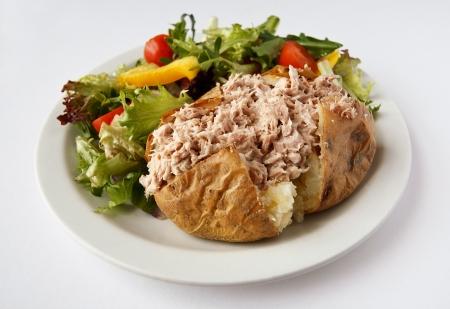 картофель: Тунец майонезом печеный картофель на тарелке с салатом стороне Фото со стока