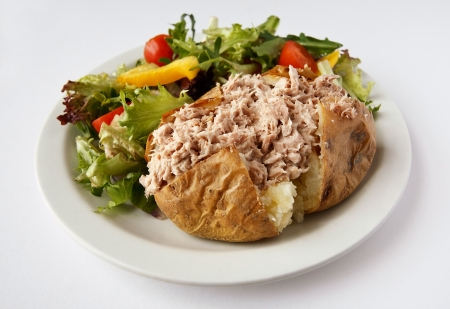 Tuna mayonnaise baked potato on a plate with side salad
