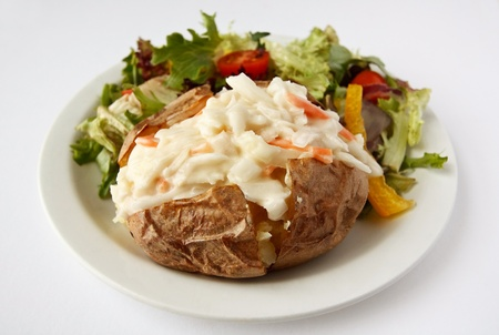 A baked potato with coleslaw filling on a plate with side salad