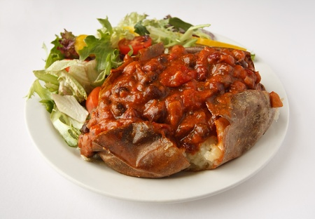 A beef chilli baked potato on a plate with side salad Stock Photo