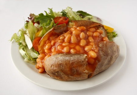 A baked bean baked potato on a plate with side salad