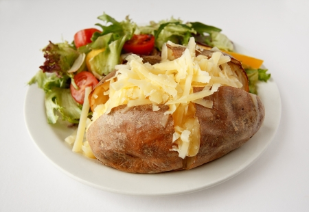 A Cheddar cheese baked potato on a plate with side salad Stock Photo