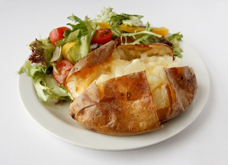 A plain butter baked potato on a plate with side salad