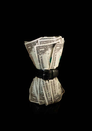 austerity: Dollar bills squeezed by belt symbolising a tight economy