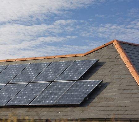 solar roof: Photovoltaic Solar panels Mounted on a slate roof of residential or private home Stock Photo