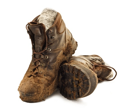 Par de botas de color marrón sucio a pie en el barro apelmazado aislado en un backgound blanco Foto de archivo