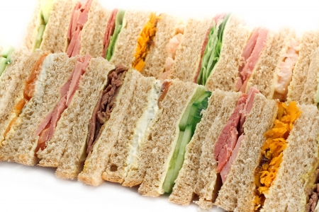 deli sandwich: Rows of sandwiches made with sliced bread and cut into triangles