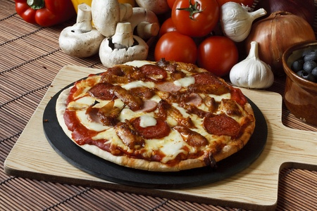 Barbecue or BBQ meat feast pizza with a topping of pepperoni, sausage, salami and chicken wings photo