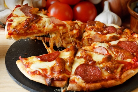 Meat feast Barbecue pizza with a topping of pepperoni, sausage, salami and chicken wings photo