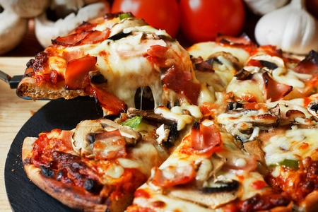 pizza: serveren plakje ham en champignons pizza met close up op vezelig gesmolten mozzarella kaas