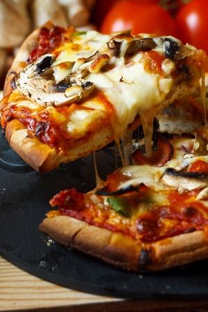 plakje ham en champignons pizza met close-up op vezelig gesmolten mozzarella kaas Stockfoto