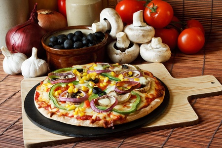 vegs: Vegetarian pizza with a topping of Mushroom, Tomatoes, peppers, onions, sweetcorn and olives Stock Photo
