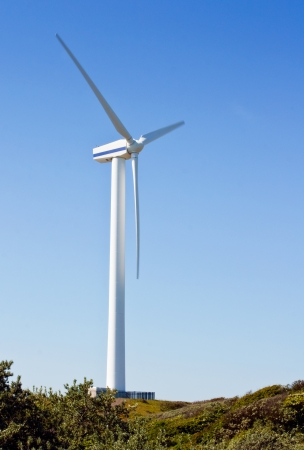 single fin: a single wind turbine used to harness renewable wind power into mechanical energy to generate electricity at wind farms, on a clear sky with text area Stock Photo