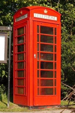 cabina telefonica: El tradicional stand de tel�fono rojo junto al tabl�n de anuncios del pueblo en un pueblo t�pico de Ingl�s