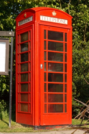 english culture: Traditional Red phone booth next to the village notice board in a typical English village
