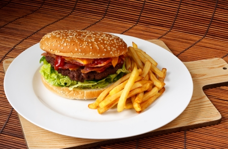 Bacon cheeseburger with a homemade beef patty on a bed of lettuce with a side of fries photo