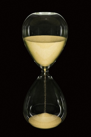 An hourglass showing the sands of time passing isolated on a black background photo