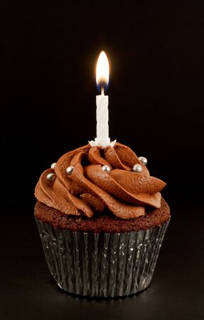 A home baked chocolate cup cake with a single lit candle to celebrate a birthday or other anniversary