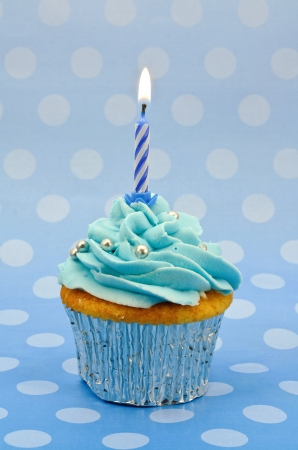 A home baked baby blue cup cake with a single lit candle to celebrate a first birthday or other anniversary Standard-Bild